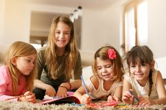 Four girls lying on the floor. Four girls lying on the floor and write their homework. Looking at camera. Looking at camera. Portrait Royalty Free Stock Photography