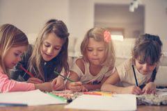 Four girls lying on the floor. Four girls lying on the floor and write their homework. Close up image Royalty Free Stock Images