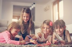 Four girls lying on the floor. Four girls lying on the floor and write their homework. Close up image of little girls Royalty Free Stock Photography