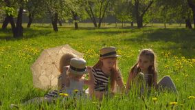 Four girls are sitting in the garden and reading. Four girls in beautiful striped dresses are sitting on the lawn in the garden and reading a book, vintage hats stock video footage