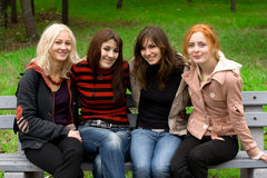 Four girls sitting on a park bench Royalty Free Stock Image
