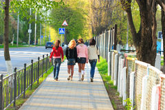 Four girls walking along the street Royalty Free Stock Photos