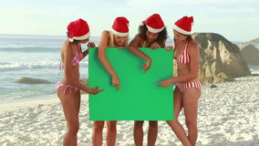 Four girls wearing christmas hats at the beach Royalty Free Stock Photography