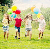 Four glad kids running on green lawn Stock Photo