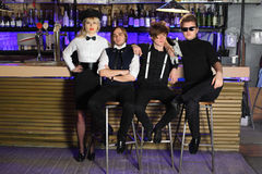 Four glamorous rock band pose near bar counte Royalty Free Stock Image