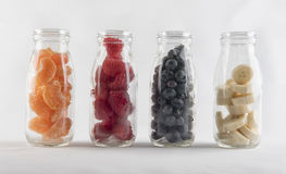 Four glass bottles filled with a mixture of fruit. Four glass bottles filled with a mixture of fruit including blueberries, oranges, banana and raspberries Royalty Free Stock Image