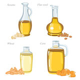 Four glass bottles with oil and oilseeds in front of them Stock Images