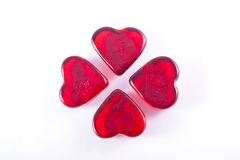 Four Glass Hearts in a Cross. Four red glass hearts presented in the shape of a cross on a white background Royalty Free Stock Photos