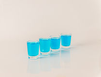 Four glasses of blue kamikaze, glamorous drink, mixed drink pour Royalty Free Stock Photos