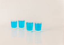 Four glasses of blue kamikaze, glamorous drink, mixed drink pour Stock Image