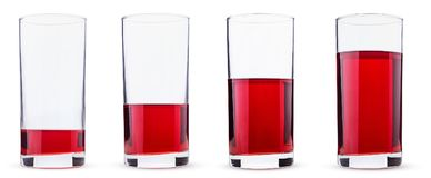 Four glasses with cherry juice, differently filled stock image