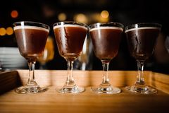 Four glasses with chocolate-colored alcoholic cocktails and white foam Royalty Free Stock Images
