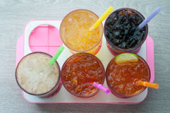 Four glasses of cold, fresh, homemade sodas with ice and drinkin. G straws against a white background. Flavors include orange, raspberry, cola and vanilla ginger Stock Images