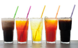 Four glasses of cold, fresh, homemade sodas with ice and drinkin. G straws against a white background. Flavors include orange, raspberry, cola and vanilla ginger Stock Photography
