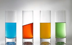 Four glasses one is different. Four glasses with some coloured liquid and on is different stock photo