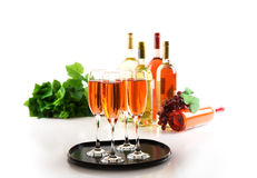 Four glasses of pink sparkling wine. And wine bottles Stock Images