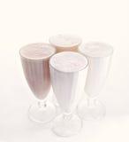 Four glasses of various milkshakes chocolate, strawberry and vanilla isolated on white background Stock Photos
