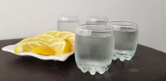 Four glasses with vodka with lemon stock images