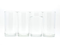 Four glasses with water in one glass Royalty Free Stock Photo