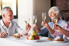 Four glasses of wine being raised at the house party Royalty Free Stock Image