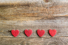 Four glitter hearts on reclaimed wood, valentines day background Royalty Free Stock Photo