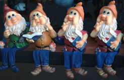 Four gnomes. In a row,sitting on a shelf royalty free stock photo