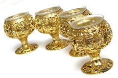 Four plastic golden colored table cup candle holders Stock Photography
