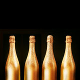 Four gold bottles of luxury champagne. Four decorative gold bottles of luxury champagne over a black background with copyspace for your New Year, Christmas or Stock Photos