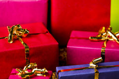 Four Golden Bows around Wrapped Presents. Tightly framed shot of plain-colored gift boxes in magenta, crimson and blue. Shallow depth of field. Background for Royalty Free Stock Photos