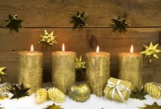 Four golden burning christmas candles for advent decoration. Royalty Free Stock Images