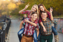 Four good friends relax and have fun in autumn park. Stock Photography