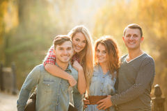 Four good friends relax and have fun in autumn park. Royalty Free Stock Photos