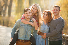Four good friends relax and have fun in autumn park. Royalty Free Stock Image