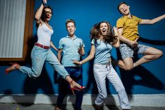 Four good-looking friends are laughing while jumping in front of the blue wall having confident and happy looks stock images