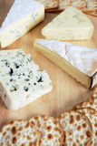 Four gourmet cheeses. With biscuits on a cheeseboard Stock Images