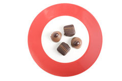 Four Gourmet Chocolates on Red Plate Royalty Free Stock Images