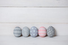 Four gray and one pink Easter egg on a wooden background. With retro filter effect Royalty Free Stock Image