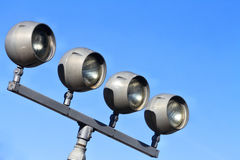 Four Gray Outdoor Spotlights on stand unlit against blue sky. Four outdoor-type spotlights are not lighted.  They are all on one stand against a blue sky Stock Photography