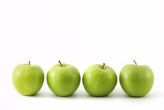 Four green apples in a row. On white Stock Photo