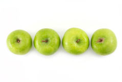 Four green apples in a row Stock Image