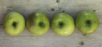 Four green apples. On woodden table in a row royalty free stock images