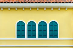Four green arched windows on yellow wall Stock Photos