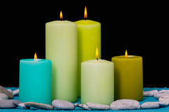 Four green candles. Four  green candles in a stone ring on a turkish surface and a black background Royalty Free Stock Photography