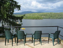 Four Green Chairs Overlooking a Lake. With tree and mountains in Quebec, Canada Royalty Free Stock Photo