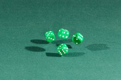 Four green dices falling on a green table. Four green dices falling on a isolated green table royalty free stock photo