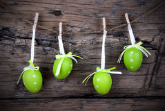 Four Green Easter Eggs With Frame. Four Green Easter Eggs Hanging On A Line On Wooden Background, Vintage Stock Photos