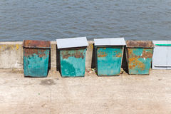 Four (4) green garbage containers standing on the stone embankme Royalty Free Stock Images