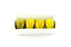 Four Green Olives in a Dish. Four green olives in a small dish on a white background Royalty Free Stock Images