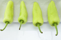Four green peppers in composition on white plate Stock Photo