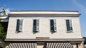 Four Green Shutters on Old Yellow Siding Stock Image